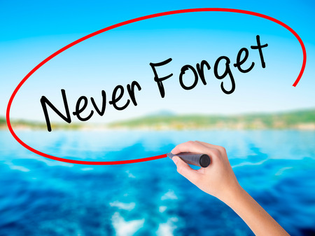 Woman Hand Writing Never Forget  on blank transparent board with a marker isolated over water background. Business concept. Stock Photo