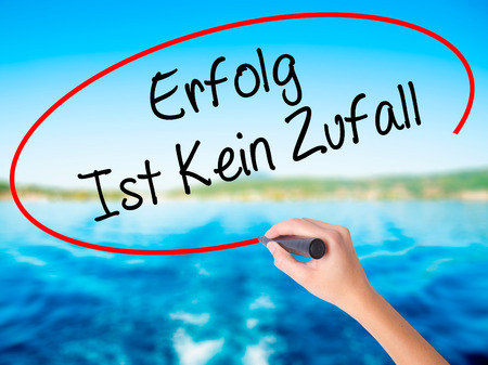 Woman Hand Writing Erfolg Ist Kein Zaufall (Success Is No Accident in German) on blank transparent board with a marker isolated over water background. Business concept. Stock Photo Stock Photo