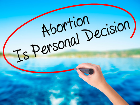 poronienie: Woman Hand Writing Abortion Is Personal Decision on blank transparent board with a marker isolated over water background. Business concept. Stock Photo