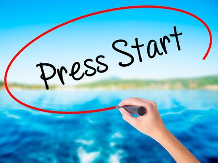 relaciones publicas: Escritura de la mano de la mujer Press Start a bordo transparente blanco con un marcador aislado sobre el fondo del agua. Concepto de negocio. Foto de stock