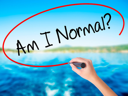 Woman Hand Writing Am I Normal? on blank transparent board with a marker isolated over water background. Business concept. Stock Photo