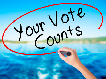 Woman Hand Writing Your Vote Counts on blank transparent board with a marker isolated over water background. Business concept. Stock Photo Stock Photo