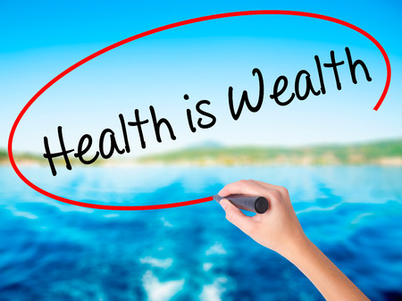 Woman Hand Writing Health is Wealth on blank transparent board with a marker isolated over water background. Business concept. Stock Photo