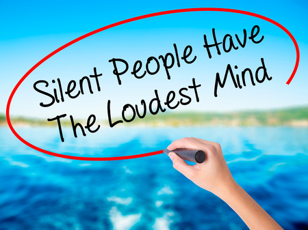 Woman Hand Writing Silent People Have The Loudest Mind on blank transparent board with a marker isolated over water background. Business concept. Stock Photo