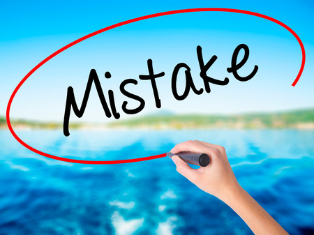 Woman Hand Writing Mistake on blank transparent board with a marker isolated over water background. Business concept. Stock Photo