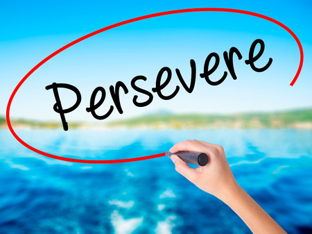 persevere: Woman Hand Writing Persevere on blank transparent board with a marker isolated over water background. Business concept. Stock Photo