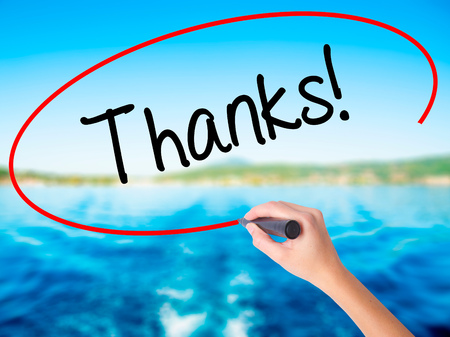 Woman Hand Writing Thanks! on blank transparent board with a marker isolated over water background. Business concept. Stock Photo