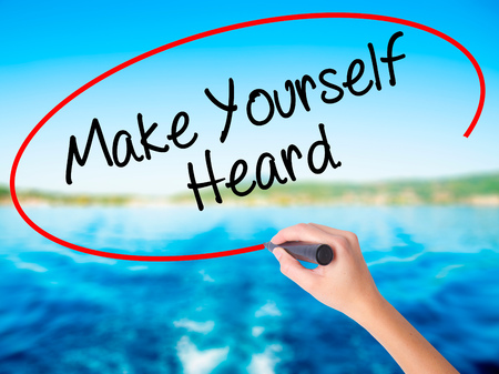 heard: Woman Hand Writing Make Yourself Heard on blank transparent board with a marker isolated over water background. Business concept. Stock Photo