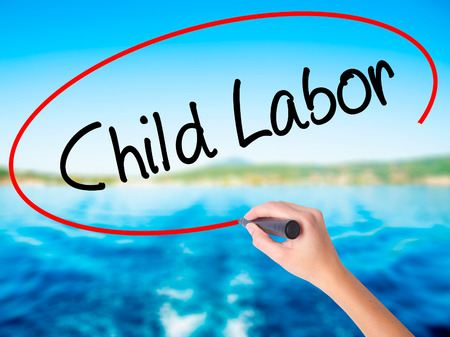 slave labor: Woman Hand Writing Child Labor on blank transparent board with a marker isolated over water background. Business concept. Stock Photo Stock Photo