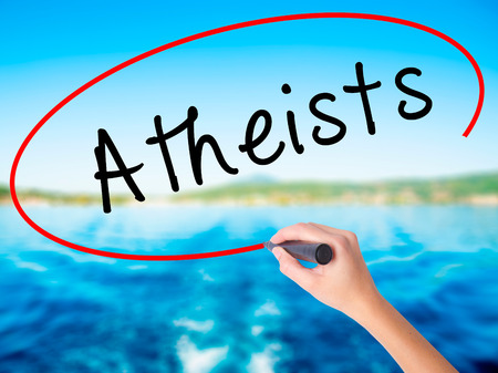 disbelieve: Woman Hand Writing Atheists on blank transparent board with a marker isolated over water background. Business concept. Stock Photo