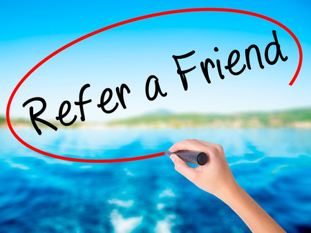 Woman Hand Writing Refer a Friend  on blank transparent board with a marker isolated over water background. Business concept. Stock Photo