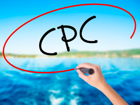 cpc: Woman Hand Writing CPC (Cost Per Click)  on blank transparent board with a marker isolated over water background. Business concept. Stock Photo