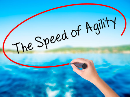 Woman Hand Writing The Speed of Agility on blank transparent board with a marker isolated over water background. Business concept. Stock Photo