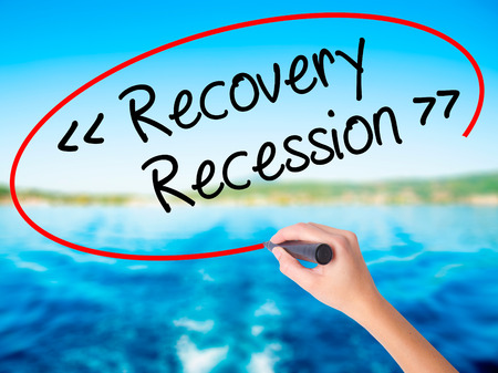 Woman Hand Writing  Recovery - Recession on blank transparent board with a marker isolated over water background. Business concept. Stock Photo