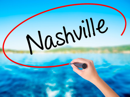 Woman Hand Writing Nashville on blank transparent board with a marker isolated over water background. Business concept. Stock Photo Stock Photo