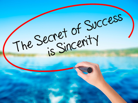 esteemed: Woman Hand Writing The Secret of Success is Sincerity on blank transparent board with a marker isolated over water background. Business concept. Stock Photo