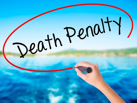 or electrocution: Woman Hand Writing Death Penalty on blank transparent board with a marker isolated over water background. Business concept. Stock Photo