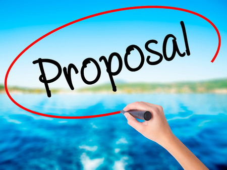 Woman Hand Writing  Proposal on blank transparent board with a marker isolated over water background. Business concept. Stock Photo