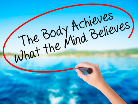 believes: Woman Hand Writing The Body Achieves What the Mind Believes on blank transparent board with a marker isolated over water background. Business concept. Stock Photo