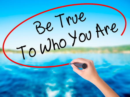 Woman Hand Writing Be True To Who You Are on blank transparent board with a marker isolated over water background. Business concept. Stock Photo Stock Photo