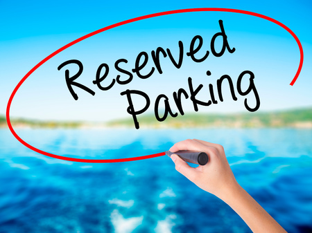 Woman Hand Writing Reserved Parking on blank transparent board with a marker isolated over water background. Business concept. Stock Photo Stock Photo