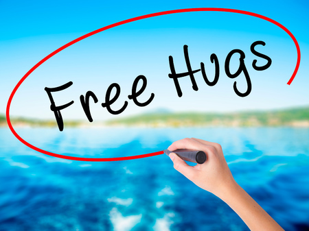 Woman Hand Writing Free Hugs on blank transparent board with a marker isolated over water background. Business concept. Stock Photo