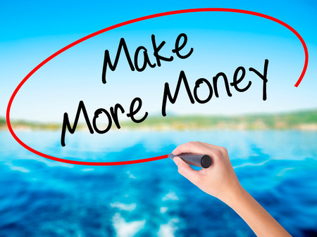 Woman Hand Writing Make Money Money  on blank transparent board with a marker isolated over water background. Business concept. Stock Photo