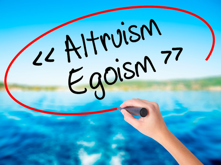 altruism: Woman Hand Writing Altruism - Egoism on blank transparent board with a marker isolated over water background. Business concept. Stock Photo