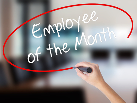 Woman Hand Writing Employee of the Month  with a marker over transparent board. Isolated on Office. Business concept. Stock Photo
