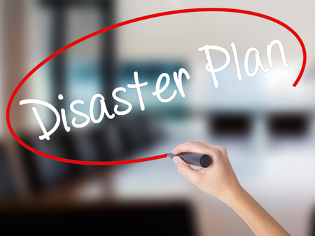 Woman Hand Writing Disaster Plan with a marker over transparent board. Isolated on Office. Business concept. Stock Photo Stock Photo