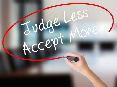 Woman Hand Writing Judge Less Accept More with a marker over transparent board. Isolated on Office. Business concept. Stock Photo Stock Photo