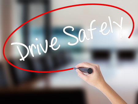 Woman Hand Writing  Drive Safely with a marker over transparent board. Isolated on Office. Business concept. Stock Photo