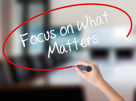 objectivism: Woman Hand Writing Focus on What Matters with a marker over transparent board. Isolated on Office. Business concept. Stock Photo