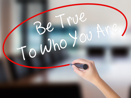 socialization: Woman Hand Writing Be True To Who You Are with a marker over transparent board. Isolated on Office. Business concept. Stock Photo Stock Photo