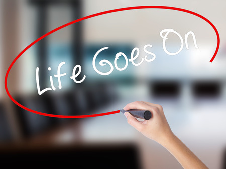 Woman Hand Writing Life Goes On with a marker over transparent board. Isolated on Office. Business concept. Stock Photo