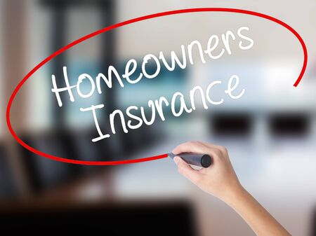 Woman Hand Writing Homeowners Insurance with a marker over transparent board. Isolated on Office. Business concept. Stock Photo