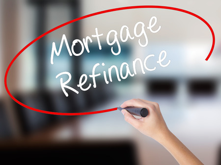 Woman Hand Writing Mortgage Refinance with a marker over transparent board. Isolated on Office. Business concept. Stock Photo