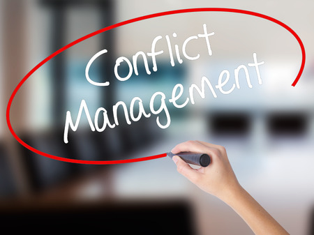 Woman Hand Writing Conflict Management with a marker over transparent board. Isolated on Office. Business concept. Stock Photo