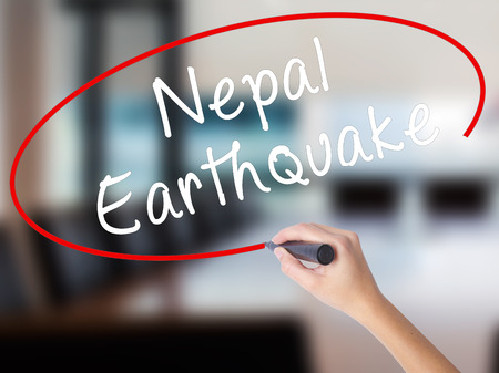 Woman Hand Writing Nepal Earthquake with a marker over transparent board. Isolated on Office. Business concept. Stock Image