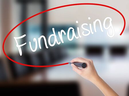 Woman Hand Writing Fundraising with a marker over transparent board. Isolated on Office. Business concept. Stock Photo