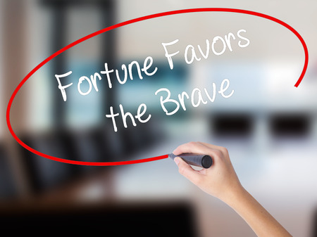 Woman Hand Writing Fortune Favors the Brave with a marker over transparent board. Isolated on Office. Business concept. Stock Photo Stock Photo