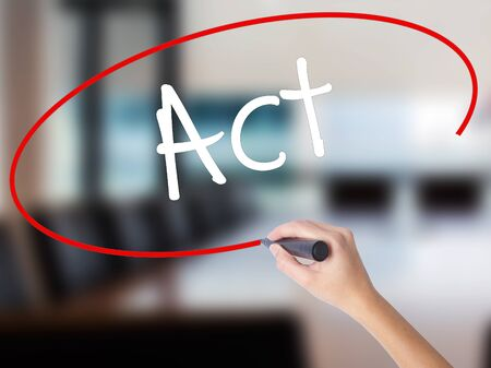 Woman Hand Writing Act  with a marker over transparent board. Isolated on Office. Business concept. Stock Photo