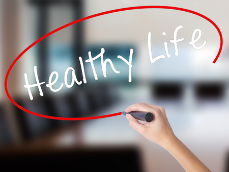Woman Hand Writing Healthy Life black marker on visual screen. Isolated on Office. Life, technology, internet concept. Stock Image Stock Photo