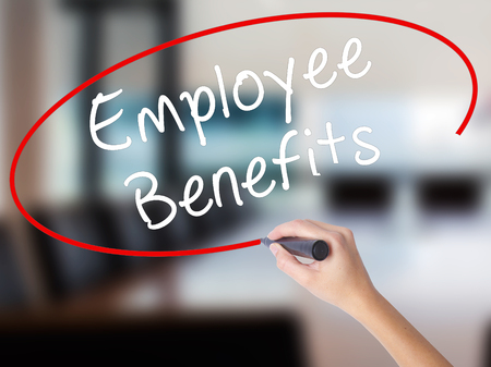Woman Hand Writing Employee Benefits with a marker over transparent board. Isolated on Office. Business concept. Stock Photo