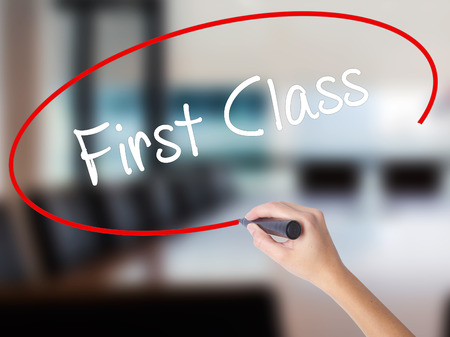 Woman Hand Writing First Class with a marker over transparent board. Isolated on Office. Business concept. Stock Photo