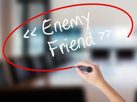 Woman Hand Writing Enemy - Friend with a marker over transparent board. Isolated on Office. Business concept. Stock Photo Stock Photo