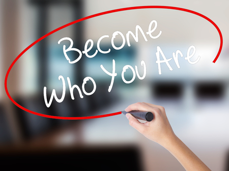 Woman Hand Writing Become Who You Are with a marker over transparent board. Isolated on Office. Business concept. Stock Photo
