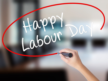 Woman Hand Writing Happy Labor Day with a marker over transparent board. Isolated on Office. Business concept. Stock Photo