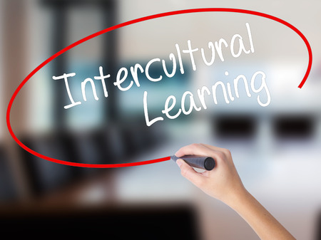 Woman Hand Writing Intercultural Learning with a marker over transparent board. Isolated on Office. Business concept. Stock Photo