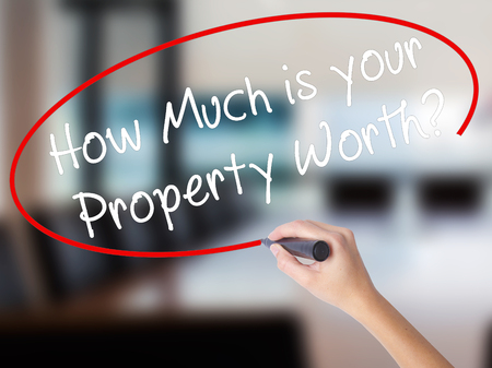 Woman Hand Writing How Much is your Property Worth? with a marker over transparent board. Isolated on Office. Business concept. Stock Image